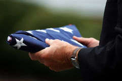 Father Holding Son's Flag. Close-up of a man's hands holding a folded American flag Royalty Free Stock Image