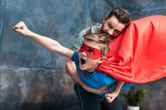Father holding son in superhero costume flying Royalty Free Stock Images