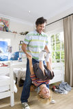 Father holding son (6-8) upside down in bedroom, smiling Stock Image