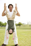 father holding son upside down in the park Stock Images