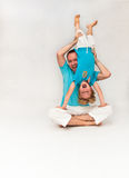 Father holding son upside down. Father sitting on the ground and holding his son upside down Stock Image
