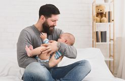 Father holding and soothing crying newborn baby in his arms. Loving daddy trying to calm crying hungry infant, babysitting at home, copy space royalty free stock photos
