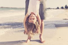 Father holding sweet young and lovely blond small daughter by her feet playing having fun on the beach in dad and little girl love. Concept enjoying Summer Royalty Free Stock Image