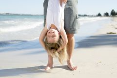 Father holding sweet young and lovely blond small daughter by her feet playing having fun on the beach in dad and little girl love. Concept enjoying Summer Royalty Free Stock Photo