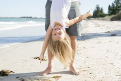 Father holding sweet young and lovely blond small daughter by her feet playing having fun on the beach in dad and little girl love. Concept enjoying Summer Royalty Free Stock Images