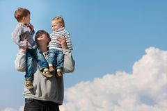 Father holding two children on his shoulders. Over sky background Stock Photo