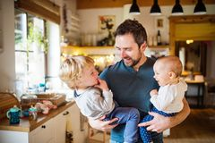 Father with two toddlers at home. Father holding two toddlers at home. Paternity leave Royalty Free Stock Photos
