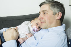 Father holding up baby girl lying on sofa, side view Royalty Free Stock Images