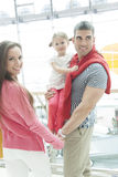 Father holding young daughter up at waist height and holding hands with mother Stock Photography