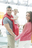 Father holding young daughter up at waist height and holding hands with mother Royalty Free Stock Image