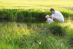 Father holds the baby above water and wets her feet Royalty Free Stock Images