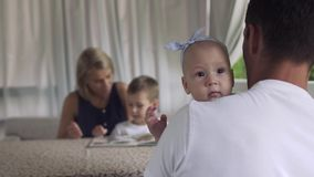 Father holds baby daughter, girl look at camera. Father in white t-shirt holds baby daughter in striped dress and bow on the head. Little girl look at camera stock video