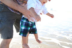 Father holds baby over waves Stock Photo