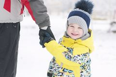 Father holds the boy`s hand in winter clothes, winter, family, hand in hand, lifestyle royalty free stock photos
