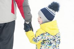 Father holds the boy`s hand in winter clothes, winter, family, hand in hand, lifestyle stock images