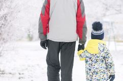 Father holds the boy`s hand in winter clothes, winter, family, hand in hand, lifestyle stock image