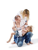 Father holds daughter and mother bends over them. Father standing on one knee holds his little daughter on hands and mother bends over them Royalty Free Stock Photos