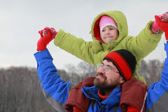 Father holds daughter on shoulders and glad royalty free stock photography