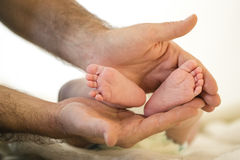 Father holds the feet of newborn baby Royalty Free Stock Image