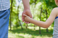 Father holds the hand of a little child in sunny park outdoor, united family concept. Nature background, shallow dof royalty free stock image