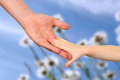 A father  holds the hand of a small child on a blue background Stock Image