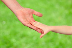 A father  holds the hand of a small child on a green background Stock Photos