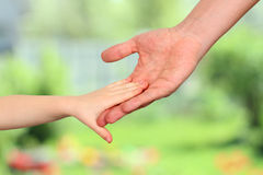 A father  holds the hand of a small child on a green background Stock Photo
