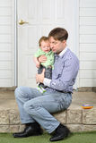 Father holds on hands crying baby, soothes and sits Royalty Free Stock Image