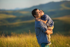 A father holds her son at the hands and smile. Together royalty free stock photography