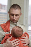 Father holds his baby by sling Royalty Free Stock Image