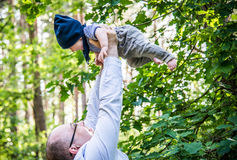Father holds his baby up in the air in forest Stock Photo