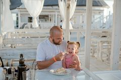 A father feeding with a spoon his little daughter while sitting at a table in a summer cafe by the sea. stock image