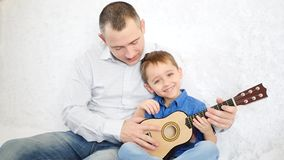 The father holds his little son and teaches him to play the guitar, the cheerful kid claps the guitar as if she plays it stock video