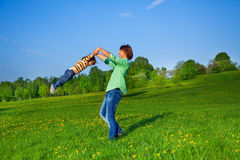 Father holds kid in the air while swirling him Stock Photos