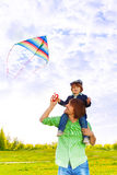 Father holds kid on shoulders with flying kite Royalty Free Stock Photo