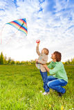 Father holds kid while watching flying kite Stock Photography