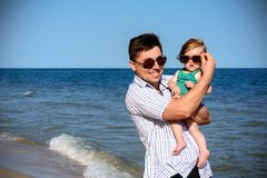 Father holds a little daughter on his shoulders in sunglasses stock photo