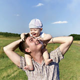 Father holds a small child on his shoulders Stock Images