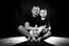 Father holds son in his arms and hugs him. Man and boy are sitting together against a black background. Happy fatherhood and. Family love royalty free stock photo