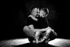 Father holds son in his arms and hugs him. Man and boy are sitting together against a black background. Happy fatherhood and. Family love stock photography