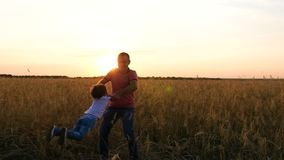 Father holds son in his arms and whirl with him. Silhouette of a happy family against the sunset.