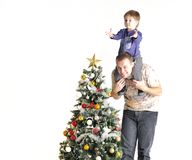 Father holds the son in one neck about a Christmas tree Royalty Free Stock Photos