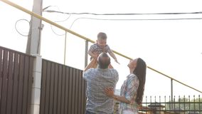 Father holds and tosses up to sky adorable little son. And mother watches standing nearby close view slow motion stock footage