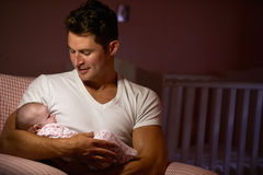 Father At Home Cuddling Newborn Baby In Nursery Stock Image