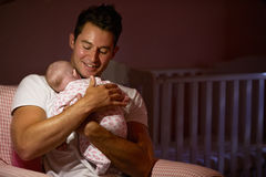 Father At Home Cuddling Newborn Baby In Nursery Royalty Free Stock Image