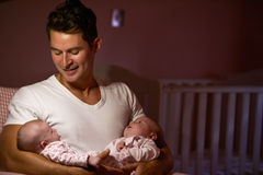 Father At Home Cuddling Twin Baby Daughters In Nursery Royalty Free Stock Images