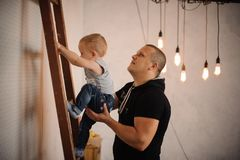 Father at home helping his little son climbing slowly up the lad. Der on the background on vintage lamps stock image