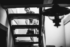 Father at home with his little son walking slowly up the stairs. Young father at home with his cute little son walking slowly up the stairs Stock Image
