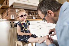 Father at home painting nails of his little daughter. stock photography