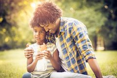 Father hug. African American father and daughter in nature. Little girl holding sandwich stock images